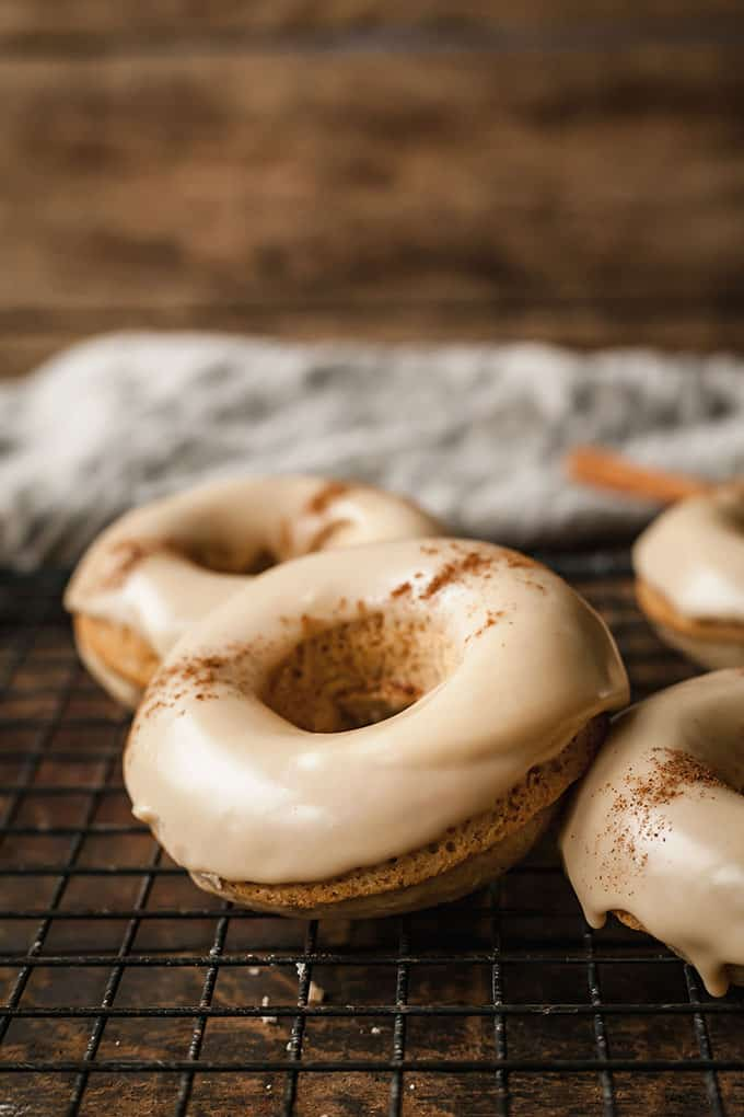 Chai Baked Donuts on a black cooling rack against a wood background with a grey linen cloth