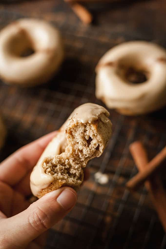 A hand holding a Chai Baked Donut with a bite taken out of it with other donuts resting in the background on a cooling rack with cinnamon sticks
