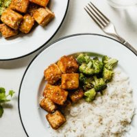 crispy tofu on a white plate with broccoli and rice