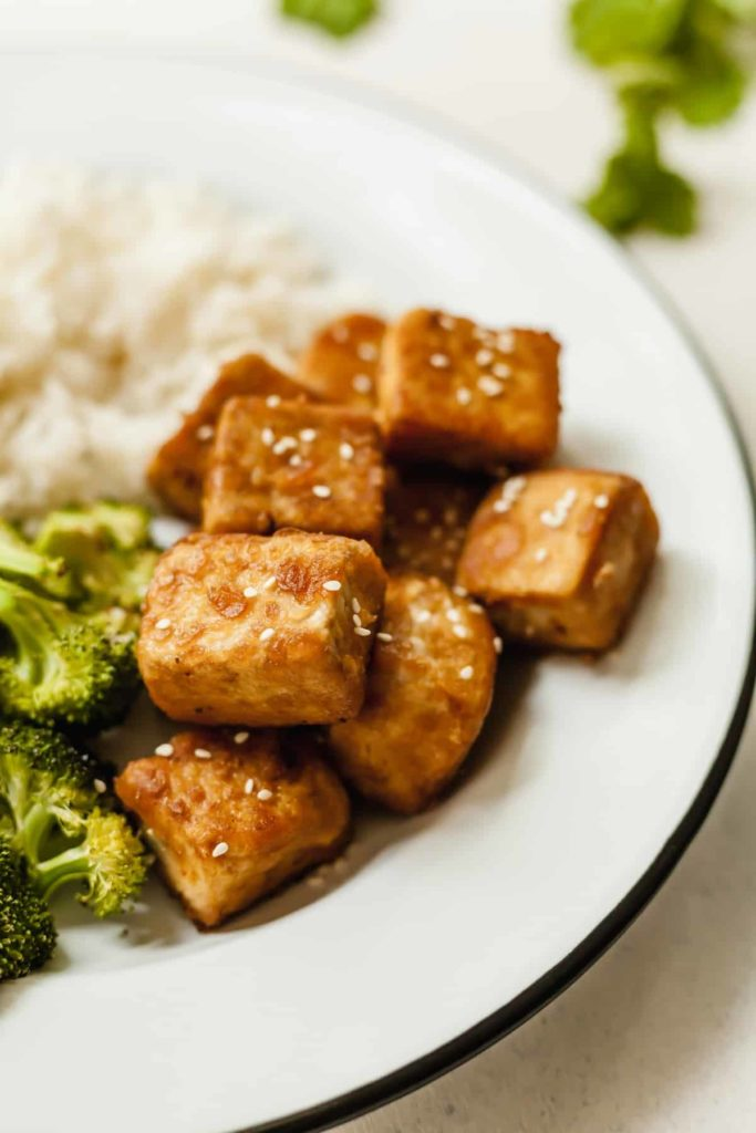 crispy tofu on a white plate with broccoli and white rice