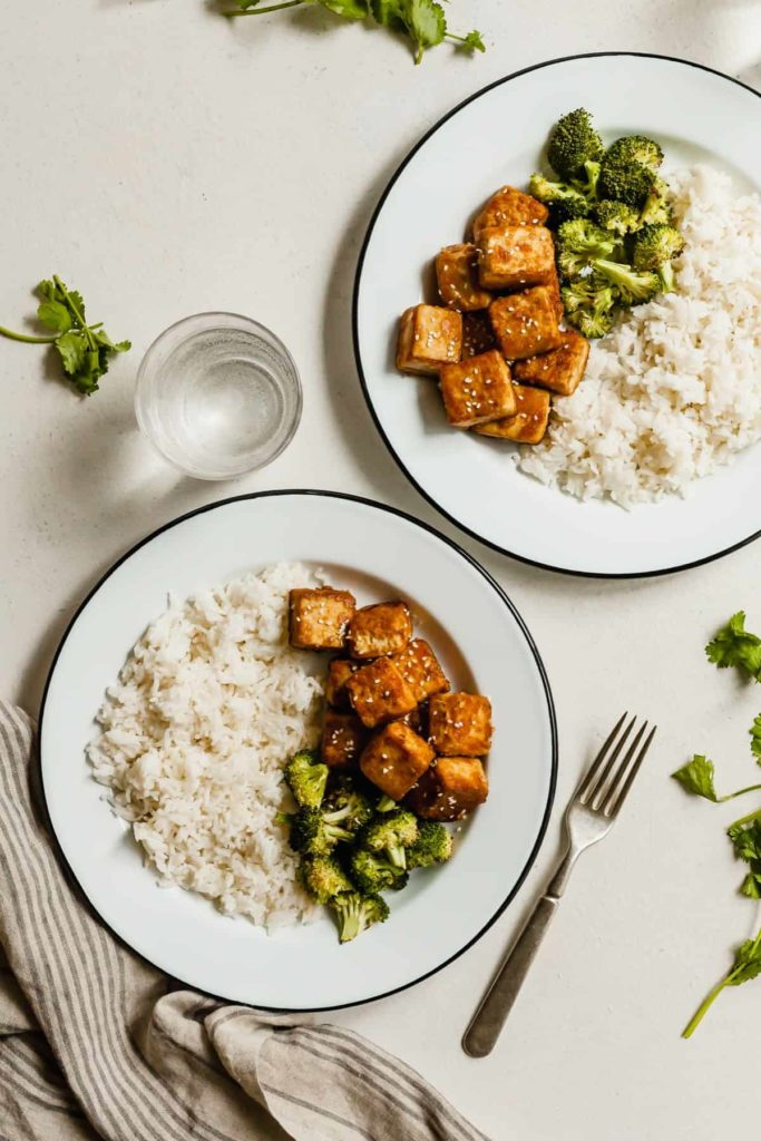 two white plates with crispy tofu, broccoli, and rice