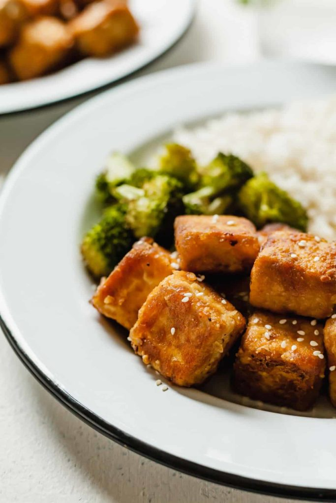 crisp tofu on a white plate with broccoli and rice