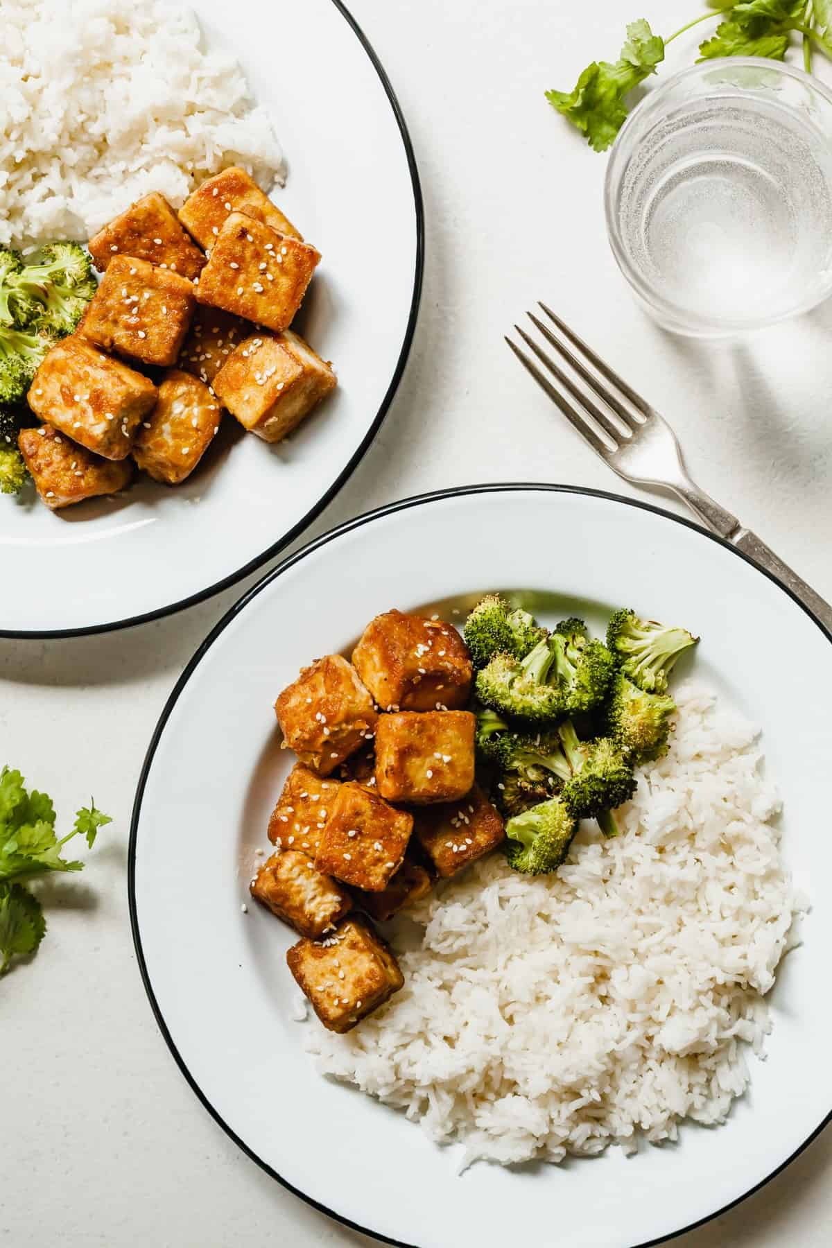 The Best Crispy Tofu served on two white plates with broccoli and rice