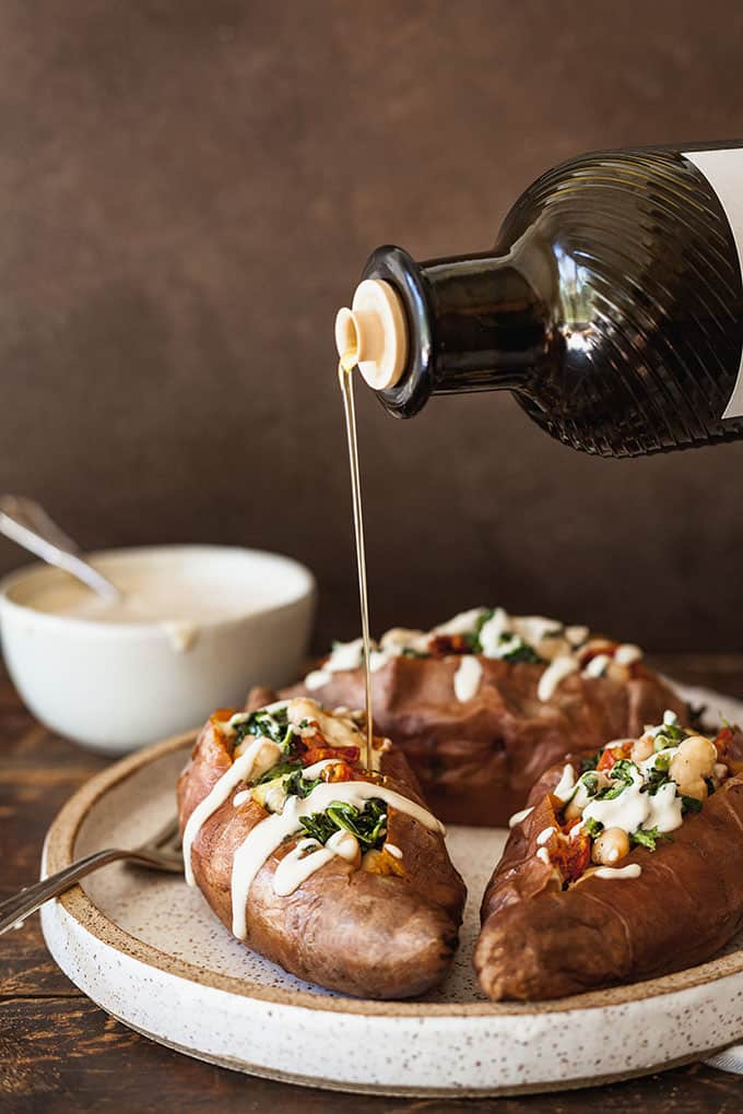 Vegan stuffed sweet potatoes with spinach and white beans being drizzled with olive oil against a dark background with a bowl of tahini sauce to the side.