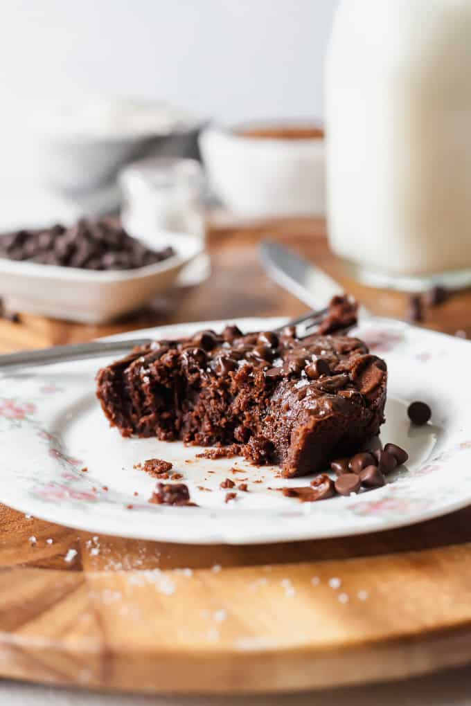 photo of a vegan single serving brownie on a white plate with pink flowers, on a wood serving tray, with chocolate chips, milk, and bowls in the background