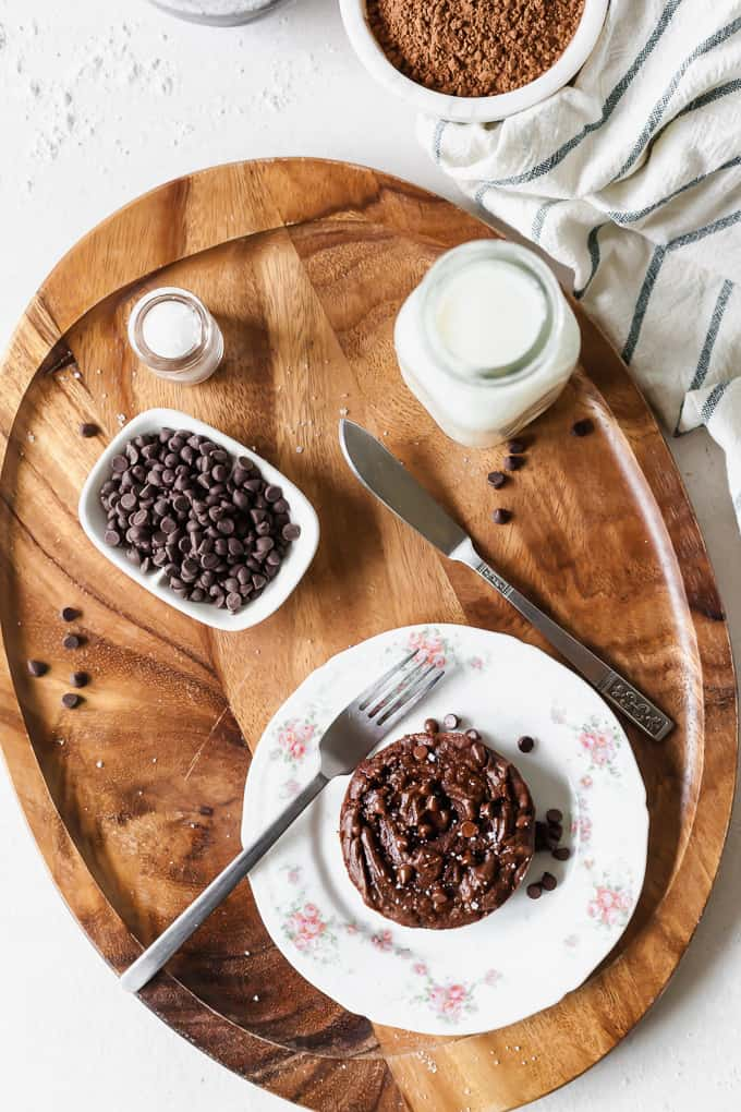 photo of a vegan single serving brownie on a white plate, with a wooden serving tray, fork, knife, chocolate chips, salt, and a glass of milk