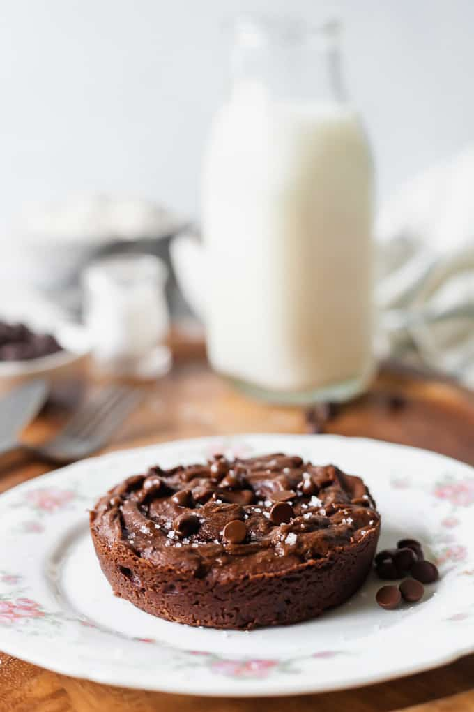 photo of a vegan single serving brownie on a white plate with pink flowers, with other kitchen items blurred out in the background