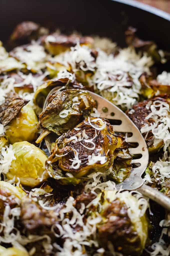close up of roasted brussels sprouts and grated parmesan on a serving spoon