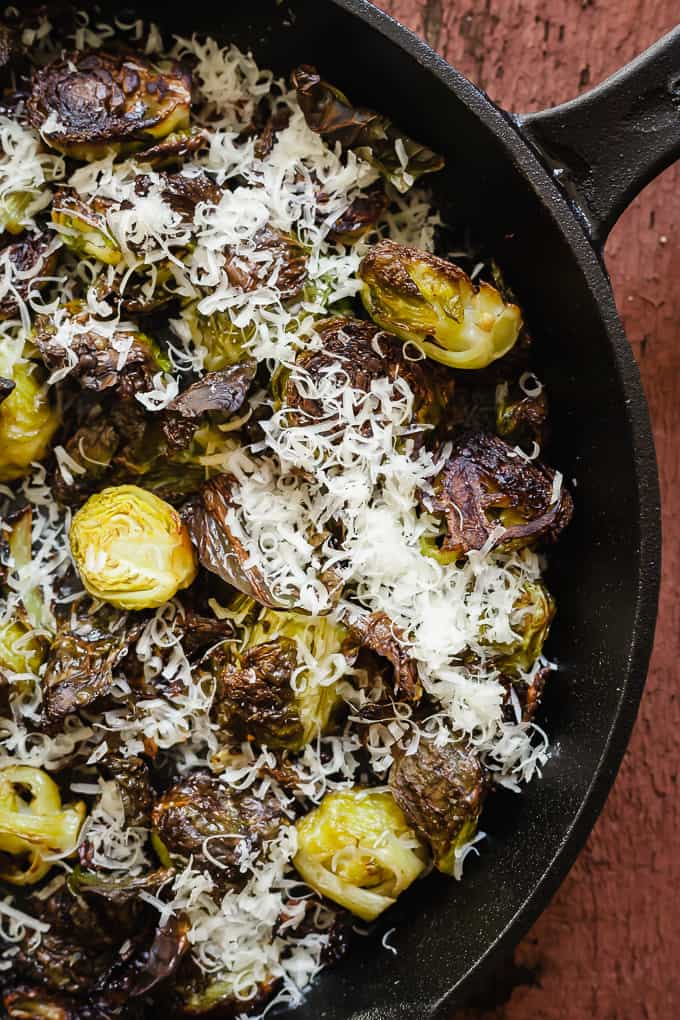 close up photo of roasted brussels sprouts with parmesan in a cast iron pan