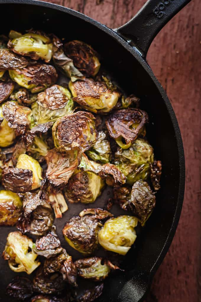 close up photo of roasted brussels sprouts in a cast iron pan