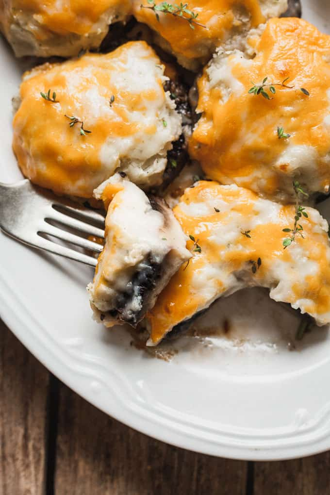 close up of white plate with a few veggiemash stuffed mushrooms and a chunk on a silver fork