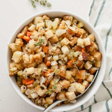 a white bowl full of vegetarian stuffing on a white background with a spoon and a striped towel