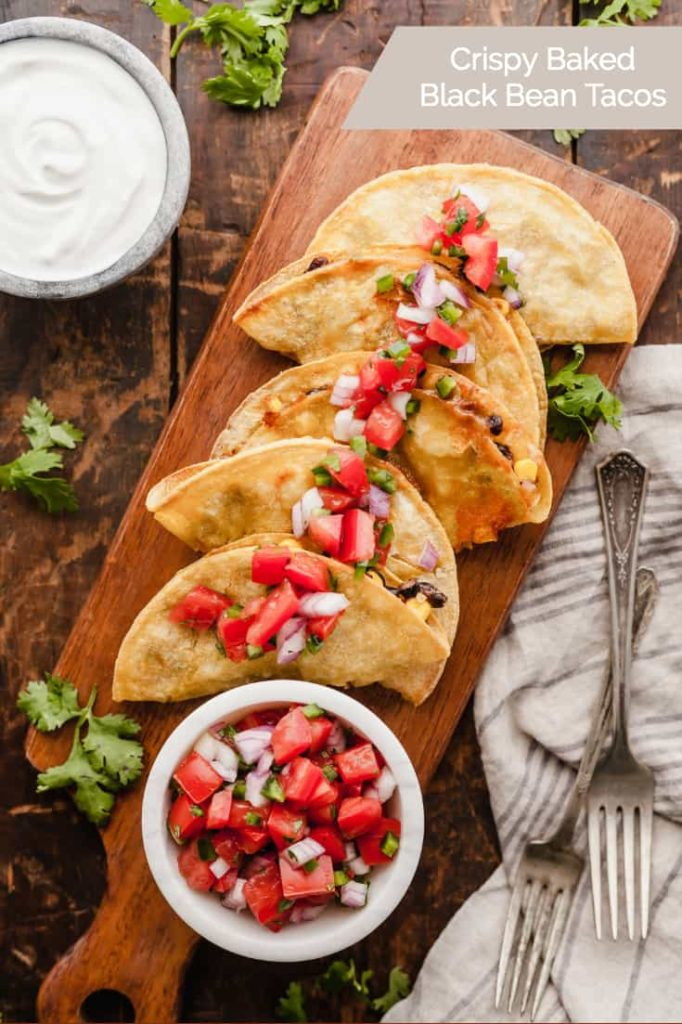 Crispy baked black bean tacos covered in pico de gallo on a wood cutting board