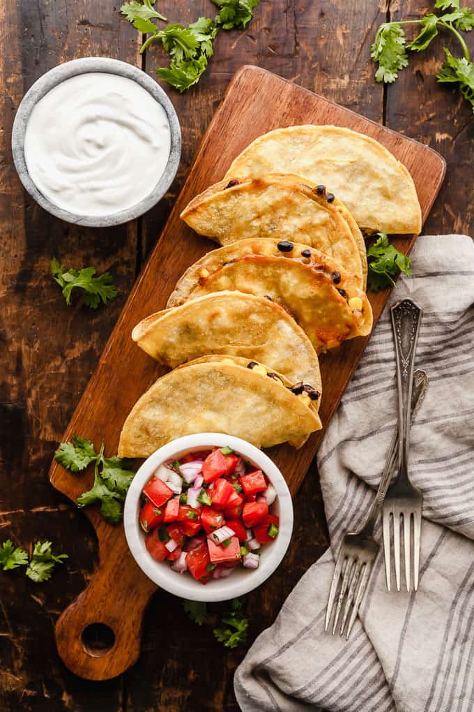 Crispy baked black bean tacos with pico de gallo and sour cream on a wood cutting board