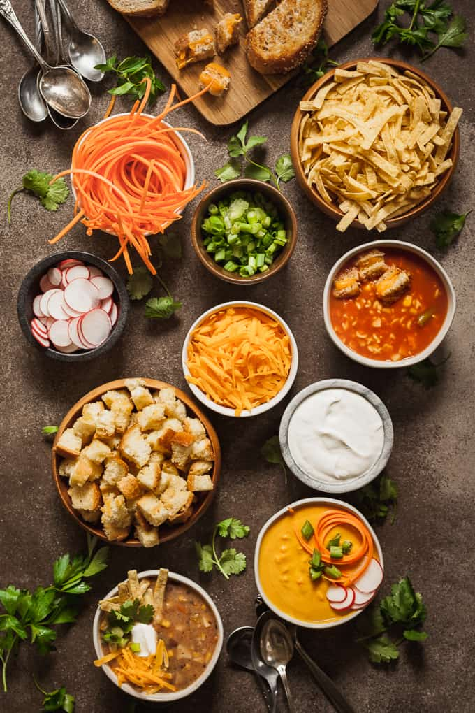 Bowls on a brown background filled with soup and toppings for a Sunday Football Soup Bar