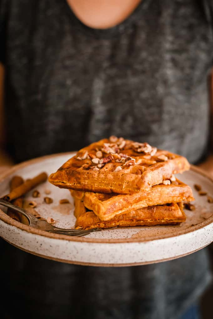 pumpkin waffles on a speckled plate being held by someone in a gray shirt