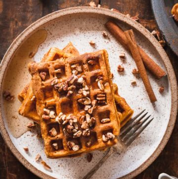 pumpkin waffles topped with pecans and maple syrup on a speckled plate on a wood background
