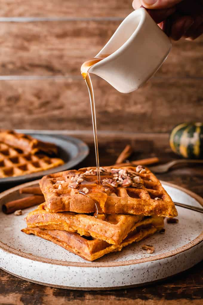 pumpkin waffles on a speckled plate with maple syrup being poured on them