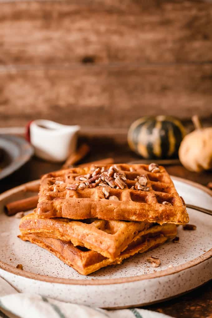 pumpkin waffles on a speckled plate topped with chopped pecans