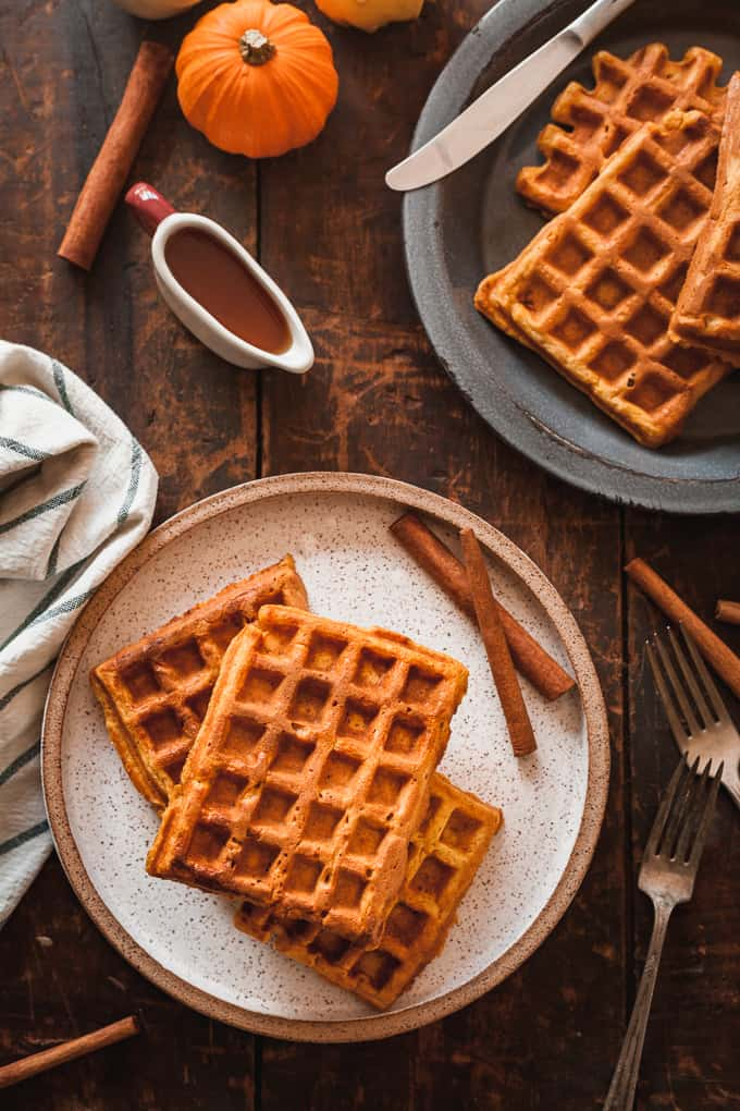 pumpkin waffles on a speckled plate and a blue plate on a wood table
