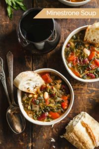 Easy Minestrone Soup in two white bowls on a wood table with bread, spoons, and wine