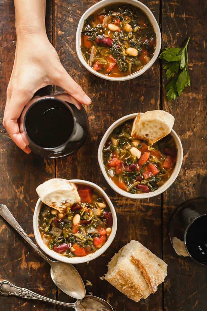 a hand grabbing a glass of red wine amidst three bowls of vegetarian minestrone soup