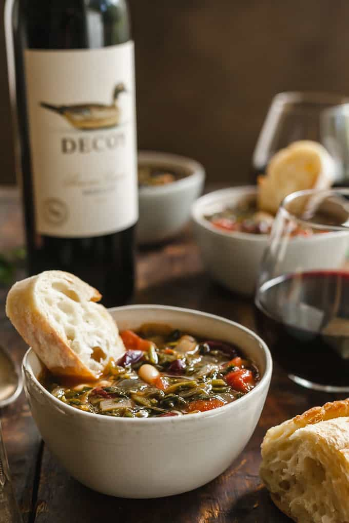 Easy Minestrone Soup in a white bowl with a slice of bread in it and wine in the background