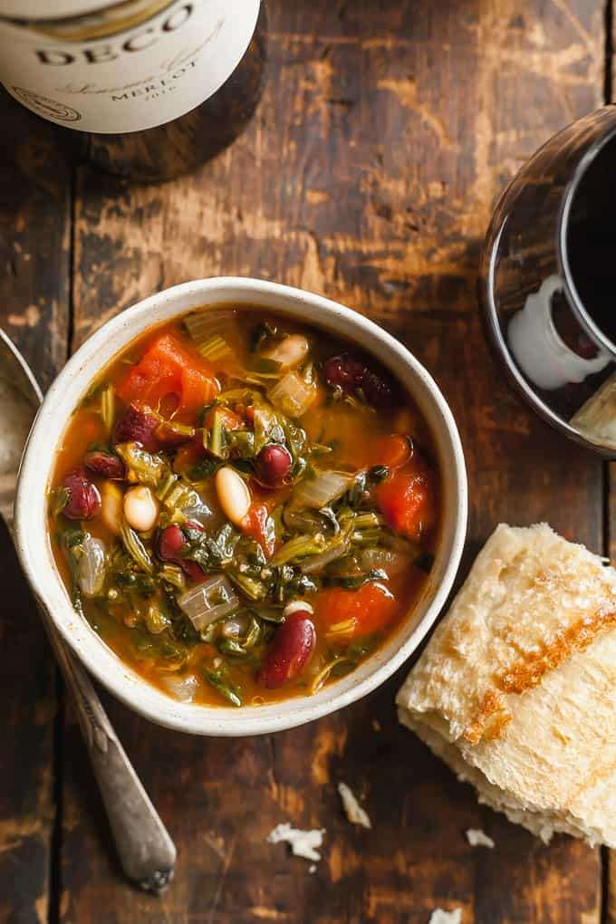 Easy Minestrone Soup in a white bowl on a wood table with a spoon, wine, and bread