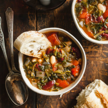 two bowls of minestrone soup with crusty bread and spoons