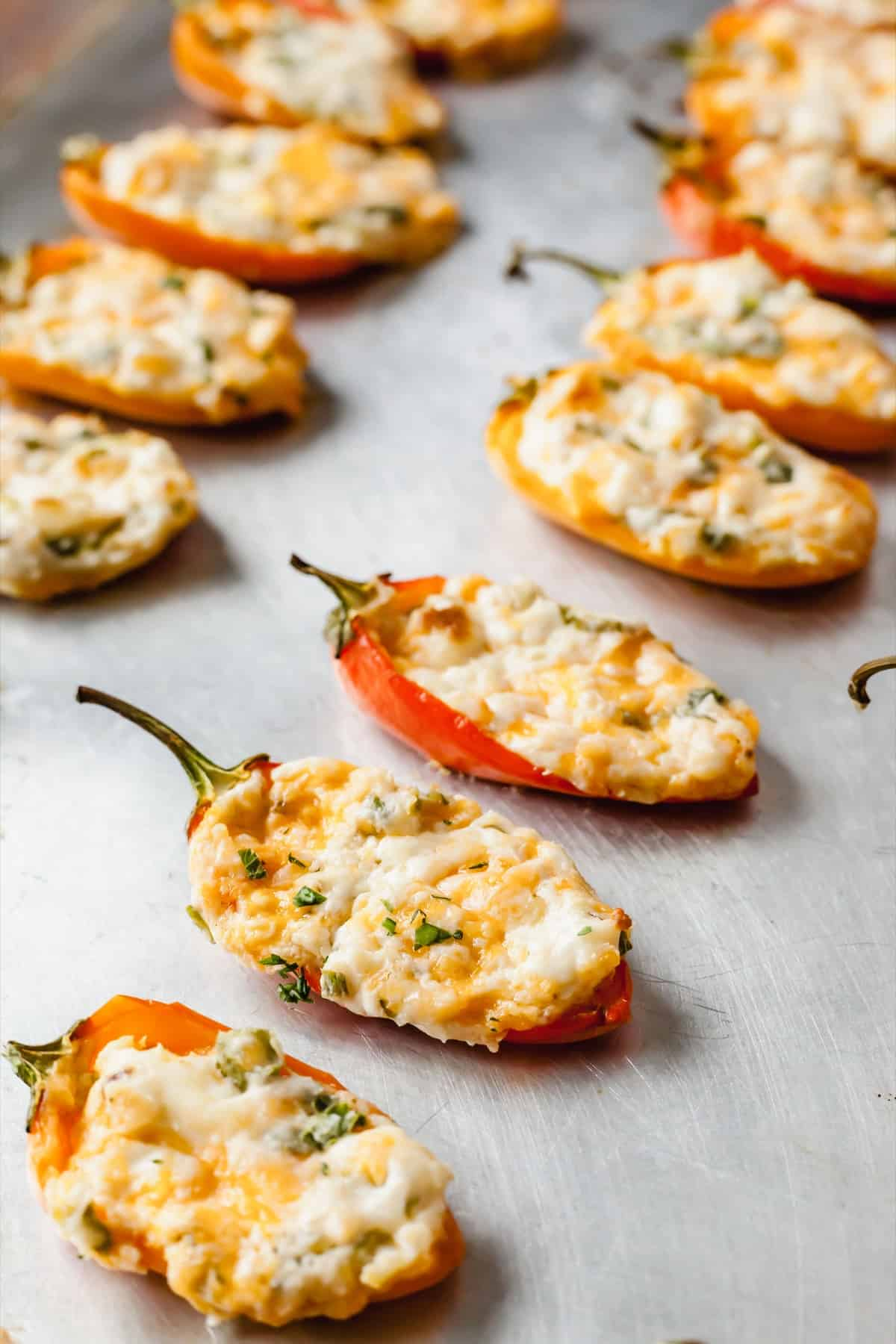cream cheese mini peppers lined up on a baking sheet