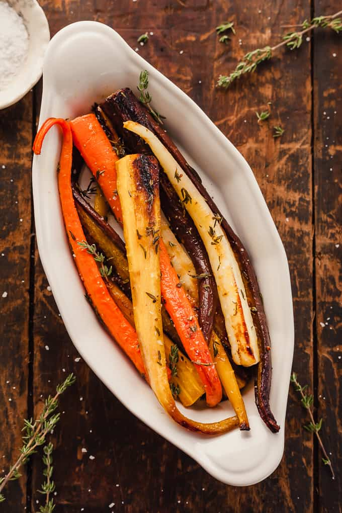 oven roasted carrots with thyme in a white dish on a wood background