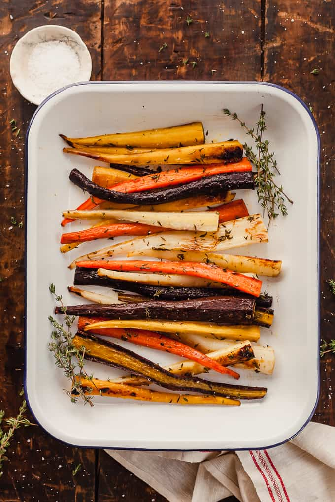a white dish of oven roasted carrots with thyme on a wood table with a dish of salt and a towel