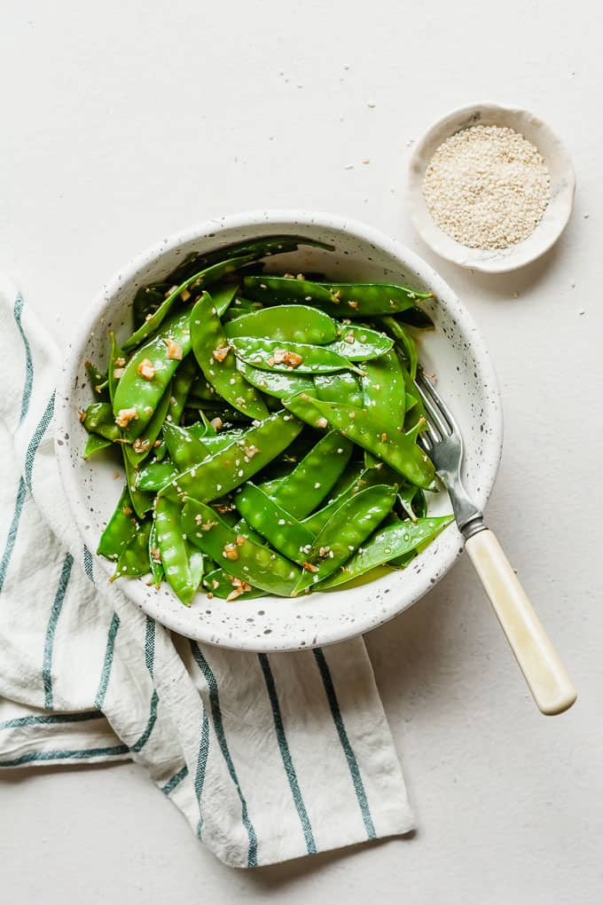 garlic ginger snow peas in a white bowl on a white background with fork, napkin, and dish of sesame seeds