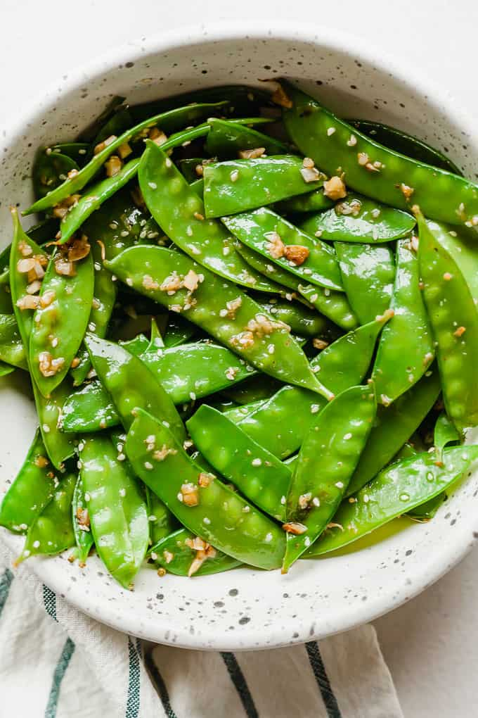 garlic ginger snow peas in a white bowl on a white background