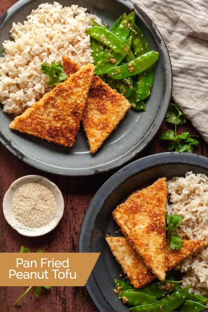 pan fried peanut tofu on blue plates with rice and snow peas