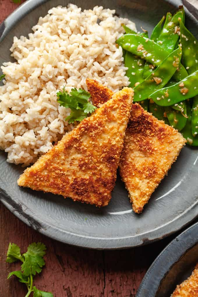 pan fried peanut tofu on a blue plate with rice and snow peas