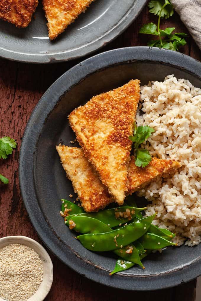 blue plate with pan fried peanut tofu, rice, and snow peas