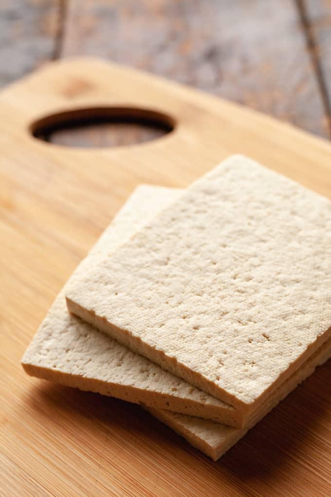 tofu slices on a wood cutting board