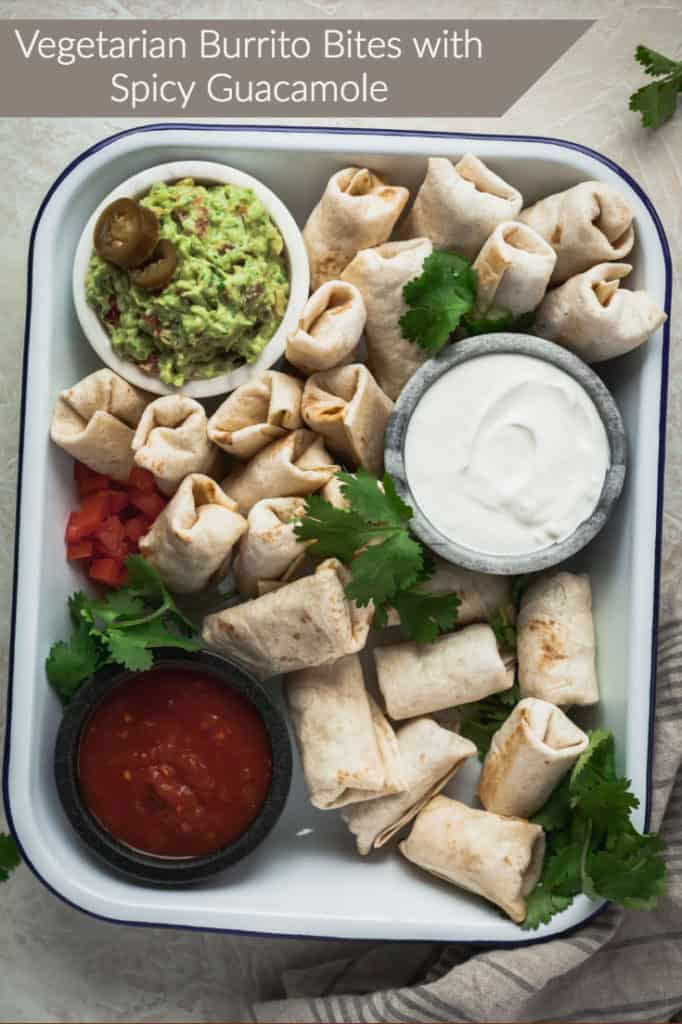 vegetarian burrito bites in a white tray with bowls of spicy guacamole, sour cream, and salsa