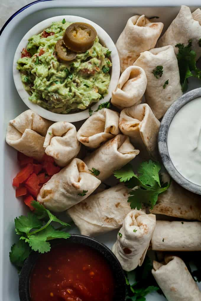 vegetarian burrito bites in a white tray with bowls of spicy guacamole, sour cream, and salsa.