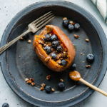 a sweet potato stuffed with blueberries, pecans, and chia seeds, drizzled with almond butter and maple syrup on a blue plate with a fork and wood spoon