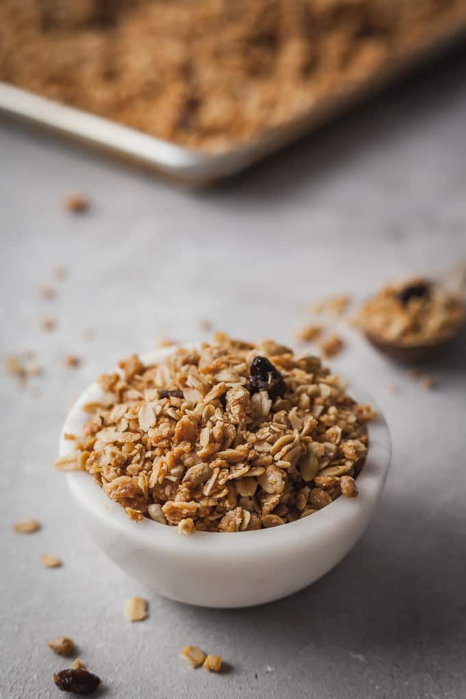 bran granola in a white bowl with a wood spoon and baking sheet in the background
