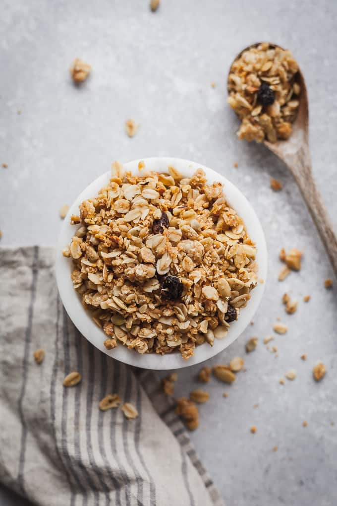 bran granola in a small white bowl with a wood spoon and towel on a gray background