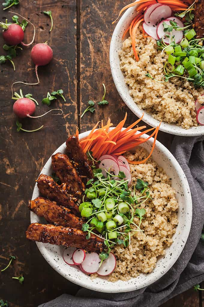 two vegan tempeh buddha bowls on a wood table with radishes