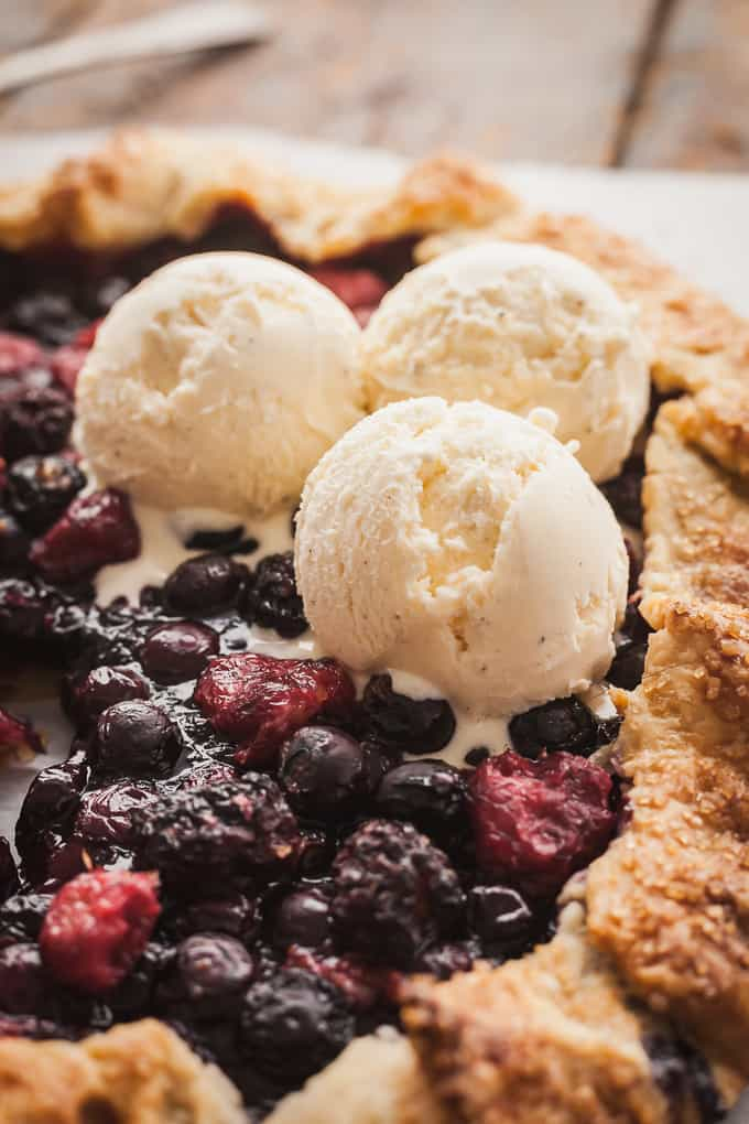 three scoops of vanilla ice cream on a mixed berry galette