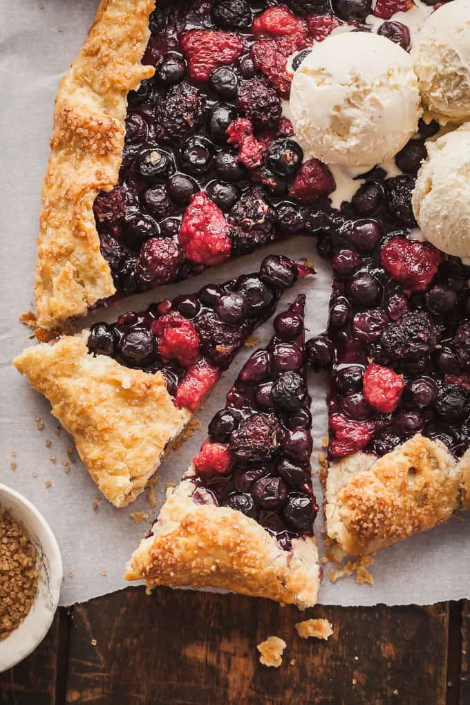 a mixed berry galette with two slices cut and some vanilla ice cream