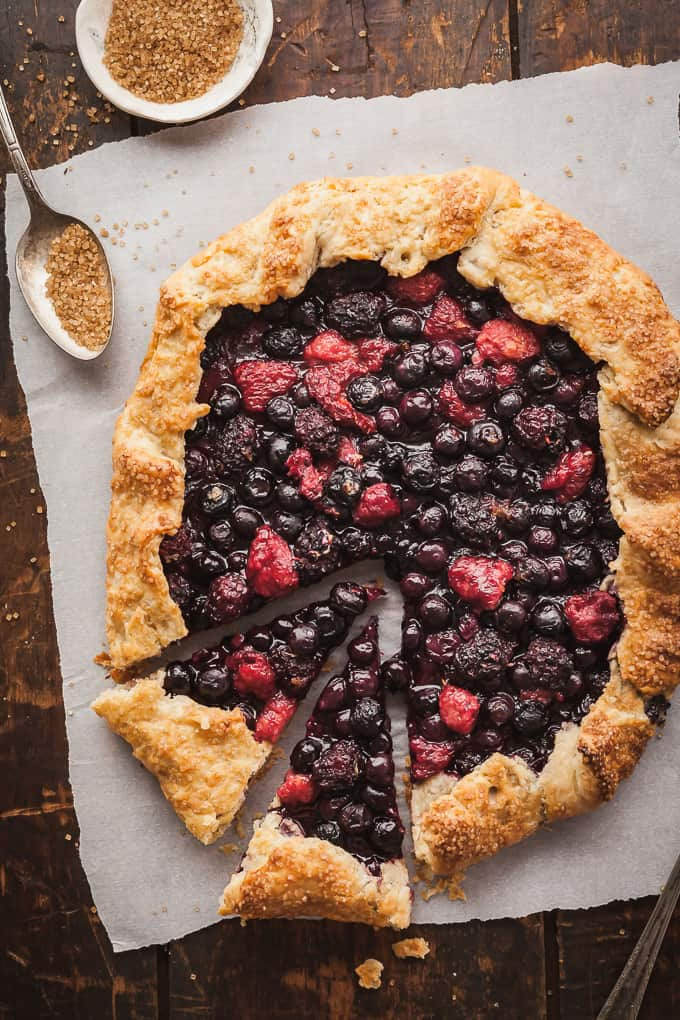 a mixed berry galette with two slices and some turbinado sugar