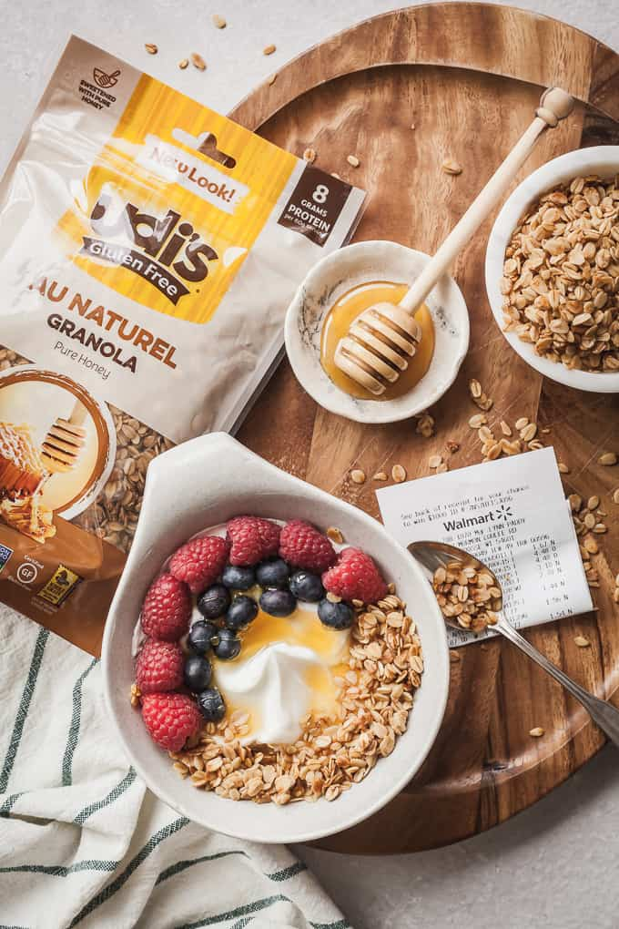 flatlay photo of a bag of granola, yogurt bowl, bowl of granola, and honey dipper on a tray