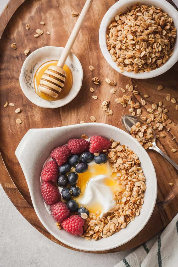 a wood serving tray with a yogurt bowl, bowl of granola, and honey dipper on a small plate