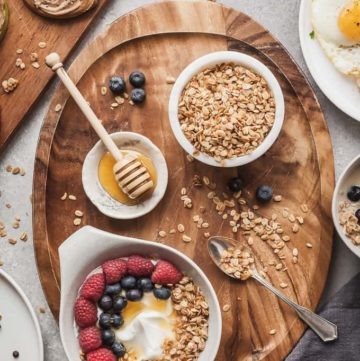flatlay photo of gluten free breakfast ideas including almond butter apple rings, a yogurt bowl, bowl of granola, and eggs